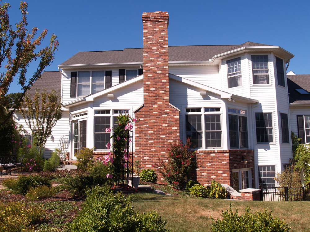 exterior home with white siding & brick chimney